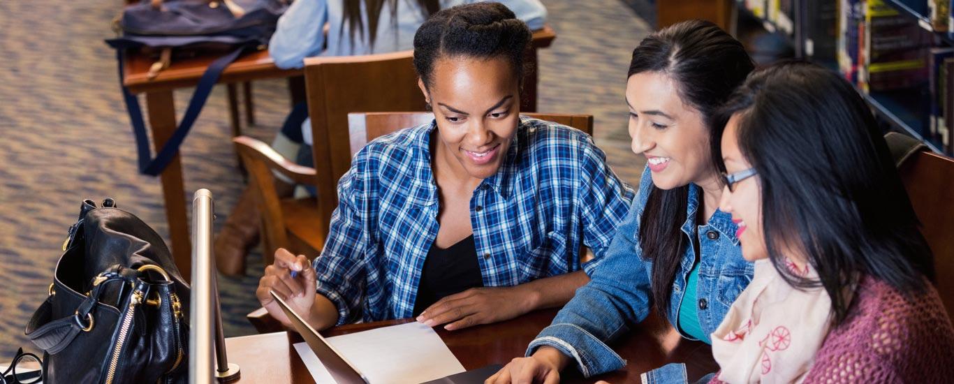 Un groupe de femmes dans une bibliothèque qui se renseignent à propos du test GEDᴹᴰ.