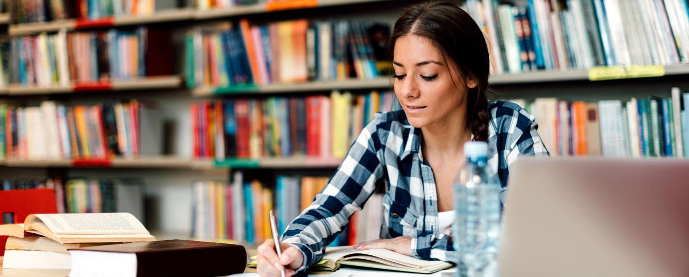 Une femme dans une bibliothèque qui étudie par elle-même pour passer le test GEDᴹᴰ.