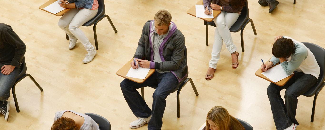Un groupe de personnes qui passent le test GEDᴹᴰ dans une salle d'étude.